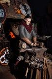 北欧海盗剑把柄剑机架再制定伪造匠战士武器成套装备轴盾皮肤火壁炉边一人 图库摄影