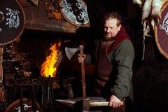 北欧海盗剑把柄剑机架再制定伪造匠战士武器成套装备轴盾皮肤火壁炉边一人 免版税图库摄影