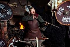 北欧海盗剑把柄剑机架再制定伪造匠战士武器成套装备轴盾皮肤火壁炉边一人 免版税库存照片