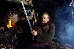 北欧海盗剑把柄剑机架再制定伪造匠战士武器成套装备轴盾皮肤火壁炉边一人 免版税库存图片
