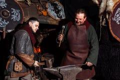 北欧海盗剑把柄剑机架再制定伪造匠战士武器成套装备轴盾皮肤火壁炉边两人 免版税库存照片