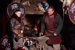 北欧海盗剑把柄剑机架再制定伪造匠战士武器成套装备轴盾皮肤火壁炉边两人 免版税图库摄影