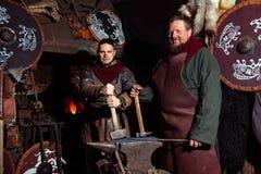 北欧海盗剑把柄剑机架再制定伪造匠战士武器成套装备轴盾皮肤火壁炉边两人 库存照片