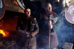 北欧海盗剑把柄剑机架再制定伪造匠战士武器成套装备轴盾皮肤火壁炉边两人 免版税库存图片