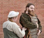 北欧海盗帮助战士的妇女投入装甲 免版税库存图片