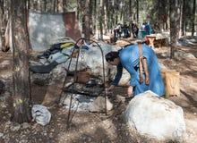 `北欧海盗村庄`的重建参加者在本Shemen附近点燃在壁炉边的火在阵营在森林里我 免版税库存照片