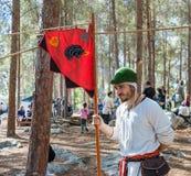 `北欧海盗村庄`的重建参加者站立与在阵营的旗子在森林里在本Shemen附近在以色列 库存图片