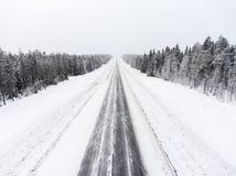 北沥青高速公路空的车道在冬天飞雪的 北卡累利阿,俄罗斯 免版税图库摄影