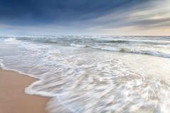 北海在沙子海滩挥动 库存图片