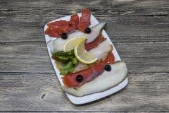 从北海大比目鱼,三文鱼的熏制的鱼纤巧 切片熏制鲑鱼和大比目鱼在一块板材有切片的柠檬 库存照片