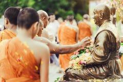 北碧泰国- 4月17日:小组修士浴菩萨雕塑4月17日净化肉与灵在Songkran节日, 免版税库存图片