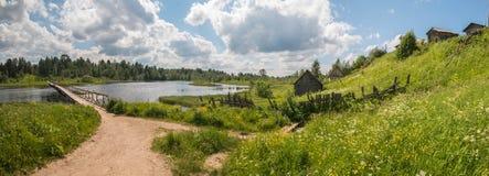北部俄国村庄 夏日,河,在海岸的老村庄 库存照片