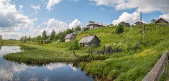 北部俄国村庄 夏日,河,在海岸的老村庄 图库摄影
