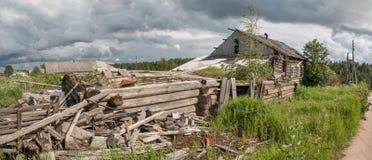 北部俄国村庄Isady 夏日, Emca河,在岸的老村庄,老木桥 被放弃的大厦 免版税图库摄影