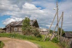 北部俄国村庄Isady 夏日, Emca河,在岸的老村庄,老木桥 被放弃的大厦 库存图片