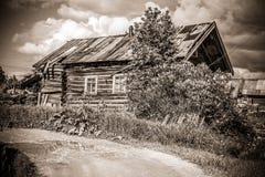 北部俄国村庄Isady 夏日, Emca河,在岸的老村庄,老木桥 被放弃的大厦 免版税库存照片