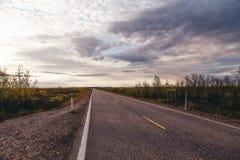 北部挪威,与在一条漫长的路的日落在凯于图凯努附近在一个夏日 免版税库存图片
