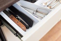 匙子、叉子和刀子在利器把抽屉装箱 免版税库存照片