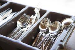 匙子、叉子和刀子在棕色塑料盒 免版税图库摄影