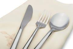 匙子、叉子和刀子在餐巾位于 免版税库存图片