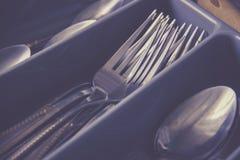 匙子和叉子在利器在厨房碗柜把抽屉装箱 免版税库存照片