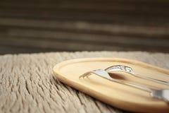 匙子和叉子在棕色木头背景  免版税库存照片