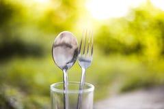匙子和叉子在水玻璃 免版税库存图片