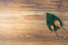 匙子和叶子在木委员会背景 使用教育的墙纸,企业照片 注意到书的产品与纸 免版税库存照片