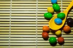 匙子和糖果在竹木样式背景 库存照片