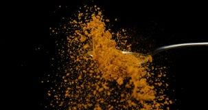 匙子和落反对黑背景,慢动作的咖喱粉 股票录像