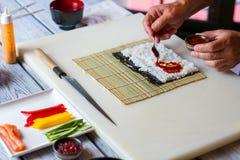 匙子投入在米上的调味汁 库存照片