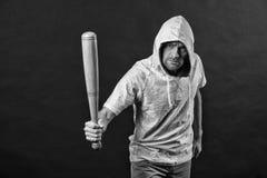 匪徒人威胁与棒武器 人举行棒球棒,侵略 小流氓在hoody,时尚的穿戴敞篷 侵略,愤怒 免版税图库摄影