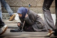 区背景中心城市设计喷泉基辅金属莫斯科俄国的购物岗位那里 5月19日, 2009边路的脚步行者和一个无家可归的饥饿的叫化子乞求为施舍 免版税库存照片
