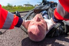 医务人员从一个受伤的骑自行车的人去除盔甲 免版税库存图片