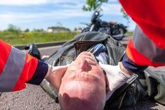医务人员从一个受伤的骑自行车的人去除盔甲 库存图片