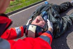 医务人员从一个受伤的骑自行车的人去除盔甲 免版税图库摄影