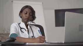医学、人们和医疗保健概念-写医疗报告的愉快的女性非裔美国人的医生或护士 股票视频