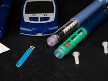 医学、糖尿病、广告和医疗保健概念-接近与血糖测试条纹,胰岛素射入的glucometer 免版税库存照片