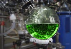 医学制造在药物工厂的 在烧瓶的绿色液体 免版税库存图片
