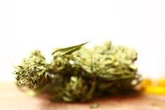 医学医药大麻绿色叶子与萃取物的在一张木桌上上油 免版税图库摄影