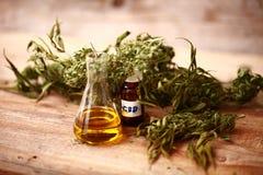 医学医药大麻绿色叶子与萃取物的在一张木桌上上油 免版税库存图片