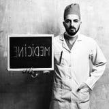 医学和补救想法 有胡子的医生拿着小的黑板 免版税库存照片