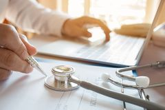 医学在膝上型计算机的医生的文字在医疗办公室 焦点stet 免版税图库摄影