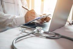 医学在膝上型计算机的医生的文字在医疗办公室 焦点stet 免版税库存图片