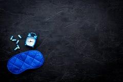 医学帮助得到睡着 好休眠 安眠药近的睡觉面具和闹钟在黑背景顶视图 免版税库存照片