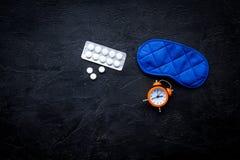 医学帮助得到睡着 好休眠 安眠药近的睡觉面具和闹钟在黑背景顶视图 库存照片