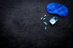 医学帮助得到睡着 好休眠 安眠药近的睡觉面具和闹钟在黑背景顶视图 免版税图库摄影