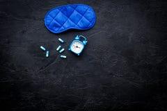 医学帮助得到睡着 好休眠 安眠药近的睡觉面具和闹钟在黑背景顶视图 图库摄影
