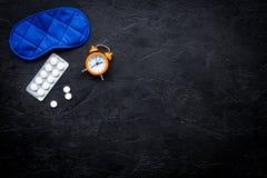 医学帮助得到睡着 好休眠 安眠药近的睡觉面具和闹钟在黑背景顶视图 免版税库存图片
