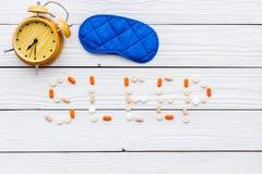 医学帮助得到睡着 好休眠 措辞睡眠标示用安眠药近的睡觉面具和闹钟在白色 免版税图库摄影